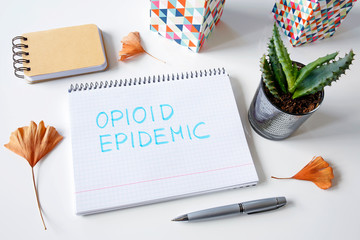 Opioid epidemic written in a notebook on white table