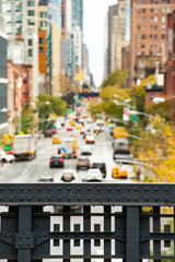 (selective focus) Blurred view from the High Line, Street traffic and buildings in Chelsea, New York, USA.