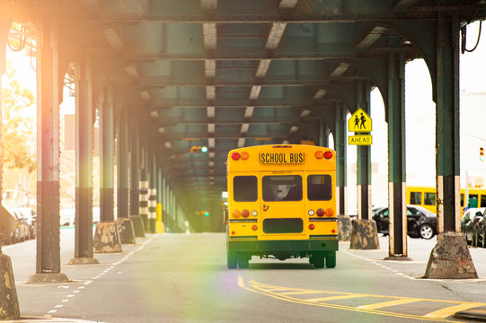 A school bus is passing under the railway bridge in the Bronx, New York city, USA.