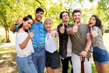 friendship and leisure concept - group of happy friends with guitar showing thumbs up at summer park