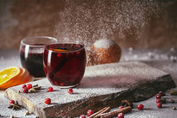 hot homemade mulled wine with cranberries with falling powdered sugar on table in kitchen