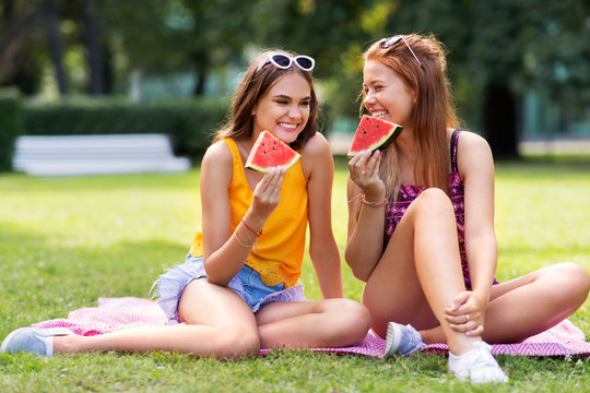leisure and friendship concept - happy smiling teenage girls or friends eating watermelon at picnic in summer park