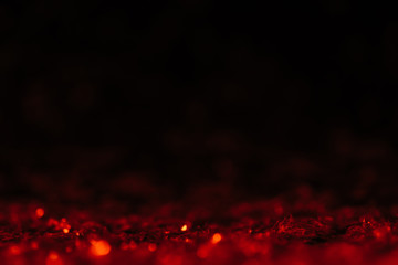 red defocused glitter on black background with copy space