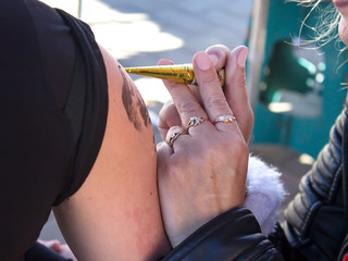 A woman applies a temporary tattoo, draws on the body with henna.
