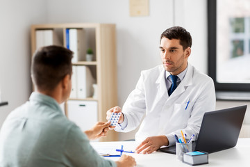 medicine, healthcare and people concept - doctor giving pills to male patient at medical office in hospital