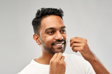 oral care, hygiene and people concept - smiling young indian man with dental floss cleaning teeth over grey background