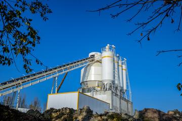 Petite cimenterie en Moselle avec son convoyeur et ses silos sous un ciel bleu
