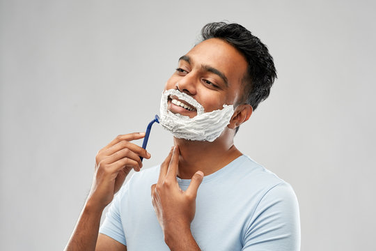 grooming and people concept - young indian man shaving beard with manual razor blade over grey background