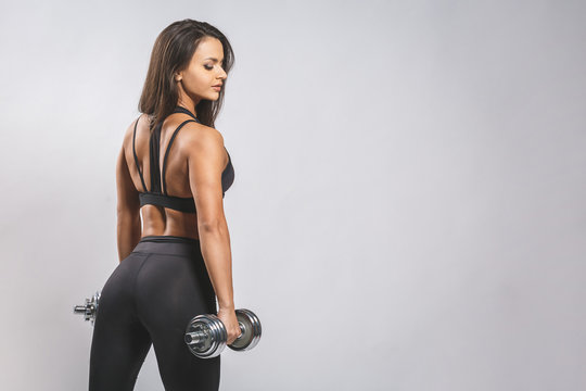 Brutal athletic woman pumping up muscles with dumbbells isolated over white background.