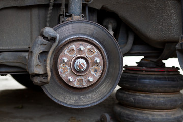 Inspection of the brake disc of an old wheel of a car raised on a jack. Worn brake disc to be replaced. The emergency state of the brake disc.