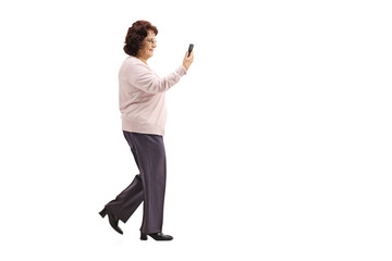 Elderly lady walking with a mobile phone