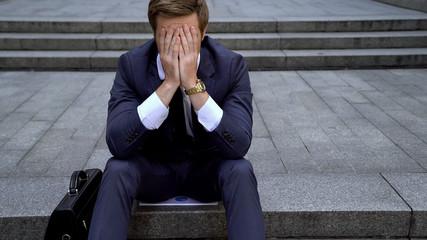 Desperate male sitting on ladder near building loosing all money on stock market