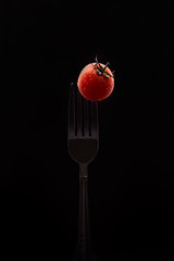 Single salad cherry tomato on fork isolated on black background