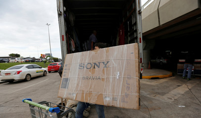 A Cuban doctor carries a large smart TV as he return to their home following severance of cooperation agreement in Brasilia
