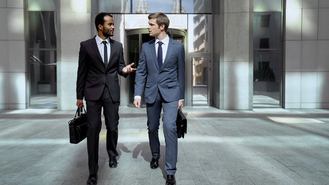 Business partners leaving office center, discussing successful cooperation