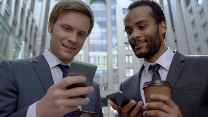 Coworkers having rest on coffee break using mobile app to search information