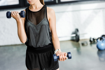 midsection of fit sportswoman training with dumbbells at gym