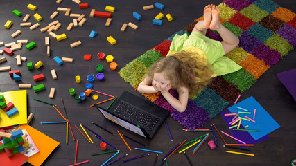 Little blond curly girl watching educational cartoon on laptop, learning numbers