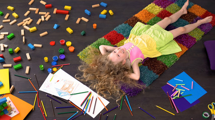 Curly blond preschool girl lying on carpet, dreaming and smiling, happy child