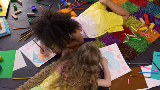 Cute curly multiracial girls lying on floor and drawing with color pencils