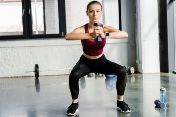 determined sportswoman doing squat exercise with dumbbell at sports center
