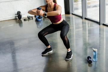 cropped view of athletic sportswoman doing squat exercise with dumbbell at fitness center