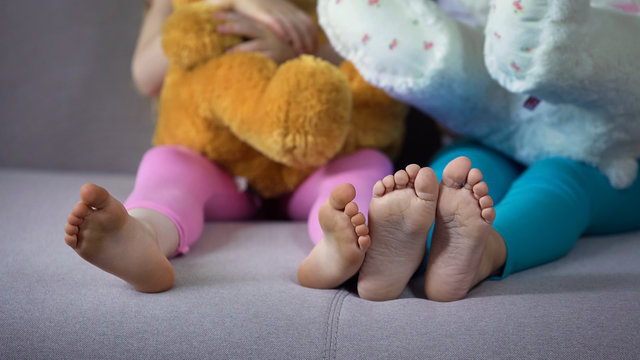Children feet closeup, multiracial friends sitting on sofa, playing with teddies