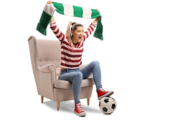 Young femal soccer fan cheering with a scarf and sitting in an armchair
