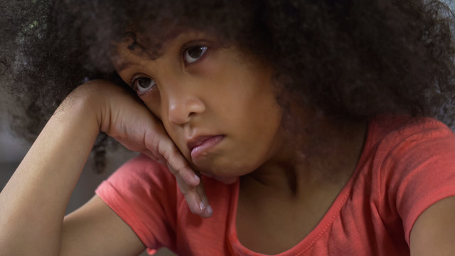 Depressed little girl sitting alone and thinking about her behavior, punishment