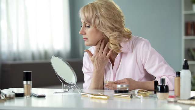 Middle-aged blond woman applying expensive makeup at home, anti-aging cosmetics
