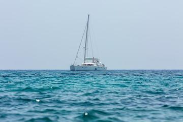 White sailing boat catamaran on ocean near beach.
