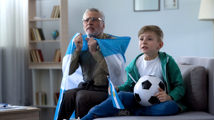 Grandpa holding Argentina flag, watching football with boy, worrying about game