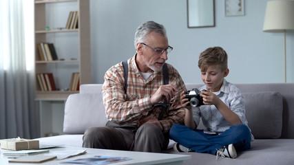 Grandpa explaining grandson how to use retro camera, young photographer dreams