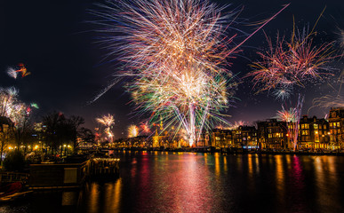 New Year's Eve fireworks in Amsterdam. Fire works over a downtown Amsterdam canal, the Amstel river