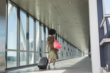 Woman with luggage bag walking at airport
