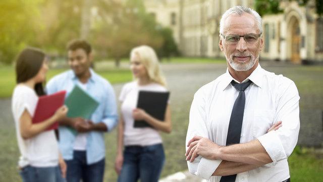 Successful professor posing with hands crossed, university education, future