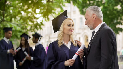 Happy blonde graduate student rejoicing diploma with father, graduation ceremony
