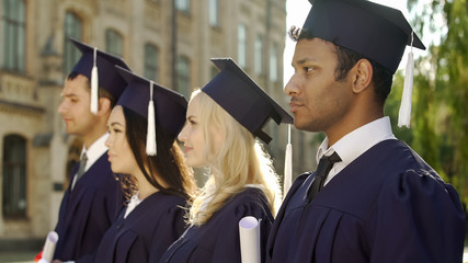 Graduate students in academic regalia standing in line and listening to speech