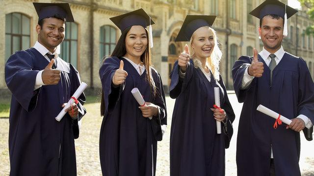 University graduates in academic regalia holding diplomas, showing thumbs-up