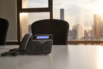 voip phone in meeting room and sun light from window