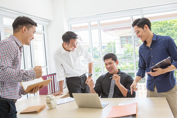 Celebrate success. Business team celebrate a good job in the office. Asian people. Business succes on mobile phone and computer. Business team. Businessman holding pen on hand.