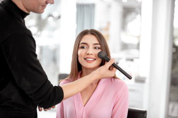 Positive happy young woman sitting in the beauty salon and feeling glad while getting powder on her face