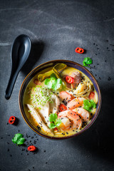 Malaysian Soup with chicken and shrimps on concrete table