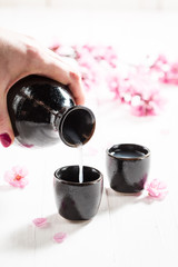 Pouring sake to dark ceramics and blooming flowers on table