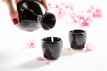 Pouring strong sake into dark ceramics on white table