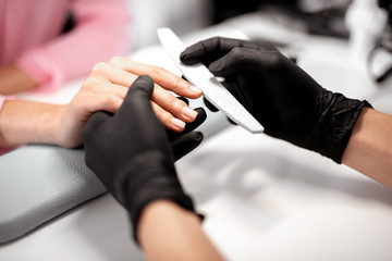 Laconic photo of professional manicurist polishing nails of female client while working
