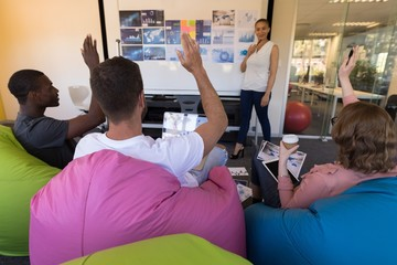 Business executives hand raised while sitting on bean bag during