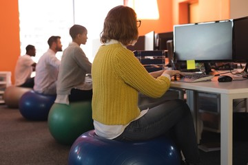 Business executives working at desk while sitting on exercise