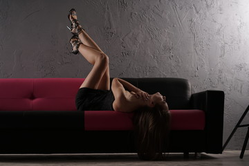 beautiful slim caucasian girl wearing little black dress sitting on the leather black sofa alone