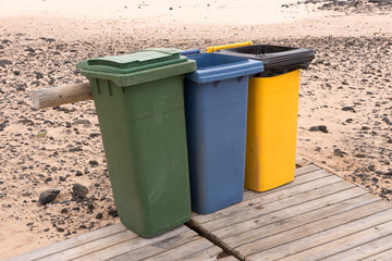 Three colorful recycle bins on the beach. Fuerteventura. Canary Islands